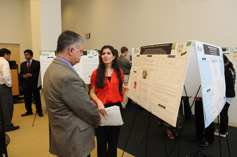 Dean Chandhoke speaking to a student at the College of Science Undergraduate Research Colloquium. Photo by Evan Cantwell/Creative Services/George Mason University