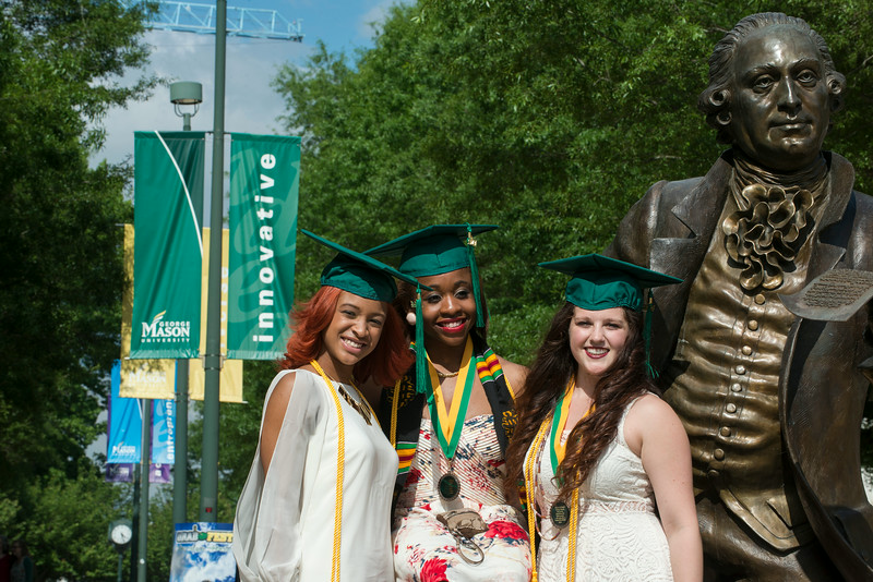 Graduates posing at the George Mason statue