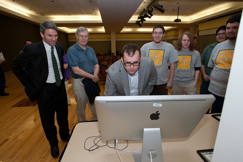 Attorney General Ken Cuccinelli watches Assistant Director of the Computer Game Design Program Seth Hudson demonstrate a game created by Mason Game Design students in Dewberry Hall at Fairfax Campus. The students created interactive and educational games aimed at teaching about the risks of joining gangs. Photo by Alexis Glenn/Creative Services/George Mason University