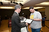 Attorney General Ken Cuccinelli gives out certificates at presentations by Mason Game Design students in Dewberry Hall at Fairfax Campus. The students created interactive and educational games aimed at teaching about the risks of joining gangs. Photo by Alexis Glenn/Creative Services/George Mason University
