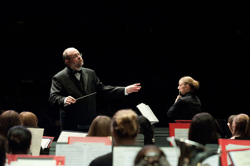 Dr. Brian C. Wuttke, Conductor, Symphonic Band, conducts the Symphonic Band as they perform at the Concert Hall on Fairfax Campus. Heather Tribble, standing at right performs as the Flute Soloist. Photo by Alexis Glenn/Creative Services/George Mason University