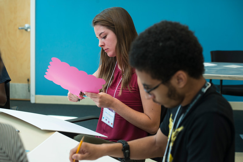 """High school students participating in the Conflict Resolution Youth Summit listen to Merri Davis' lecture titled """"The Arts as a Catalyst for Social and Political Change in America"""". Merri Davis is a Ph.D. student in the School for Conflict Analysis and Resolution. During the second part of the lecture, the students worked in groups to create cohesive art pieces that represented the social issue of their choice. Undergraduate students also helped them come to an agreement on which issue their group would illustrate. Photo by Bethany Camp / Creative Services / George Mason University"""