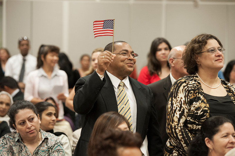 Immigrants wave American flags as they prepare to take the Oath of Allegiance to complete their U.S. citizenship process at a naturalization ceremony at Founders Hall at the Arlington campus. Photo by Alexis Glenn/Creative Services/George Mason University