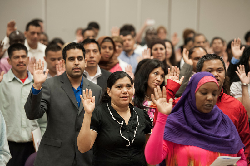 Immigrants take the Oath of Allegiance to complete their U.S. citizenship process at a naturalization ceremony at Founders Hall at the Arlington campus. Photo by Alexis Glenn/Creative Services/George Mason University