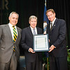 Ángel Cabrera, President, George Mason University, and Tom Davis, Rector, George Mason University Board of Visitors, honor Dwight C. Schar (center) during the Schar School of Policy and Government Dedication.  Photo by Ron Aira/Creative Services/George Mason University