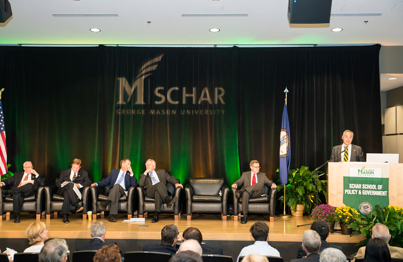 Ángel Cabrera, President, George Mason University, speaks during the Schar School of Policy and Government Dedication as Gerry Connolly, United States Representative, VA 11th District, Tom Davis, Rector, George Mason University Board of Visitors, The Honorable Joh. R. Kasich, Governor of Ohio, The Honorable Terence McAuliffe, Governor of Virginia, and Mark J. Rozell, Dean Schar School of Policy and Government, join him on stage.    Photo by:  Ron Aira/Creative Services/George Mason University