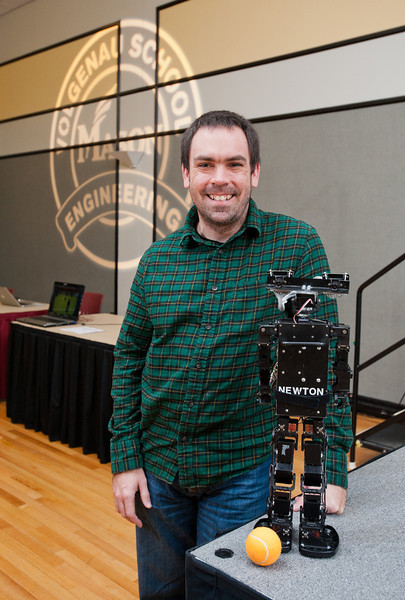 "Graduate Teaching Assistant and Undergraduate Advisor Keith Sullivan stands next to ""Newton"" a robot constructed by Mason's Robo Patriots Club, at Volgenau School's Engineers Day in Dewberry Hall at Fairfax Campus. Photo by Alexis Glenn/Creative Services/George Mason University"