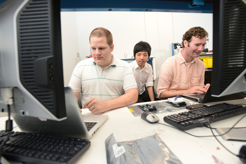 Engineering students design an anti-stutter microcontroller device under the guidance of Nathalia Peixoto, assistant professor of electrical and computer engineering, and James Brinton, a speech language pathologist at the Katherine Thomas School in Rockville, Md. Pictured left to right: Jon Posey, Steve Lim and Jim Beatty. Photo by Evan Cantwell/Creative Services/George Mason University