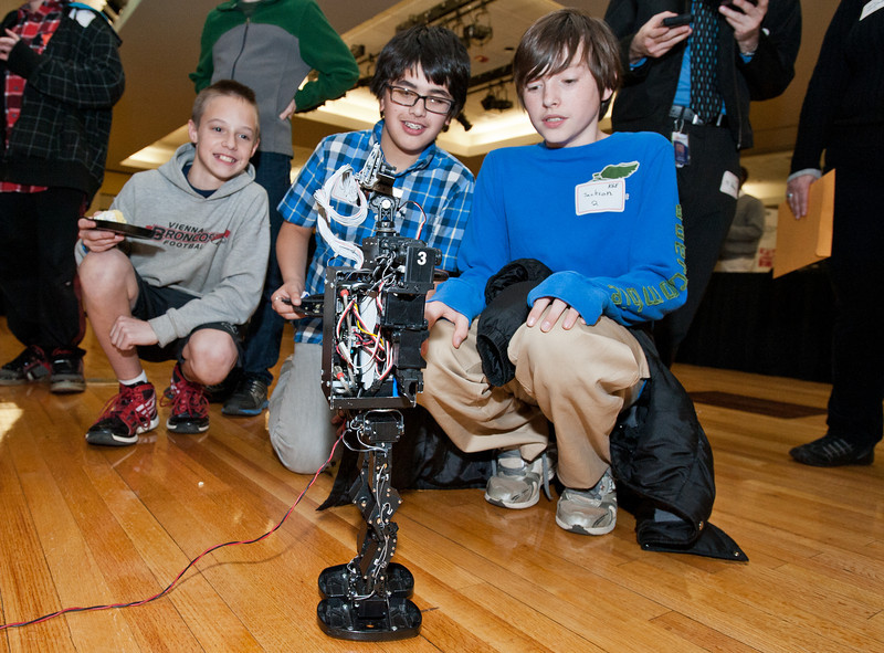 "Elementary school students watch ""Newton"" a robot constructed by Mason's Robo Patriots Club demonstrate his walking abilities at Volgenau School's Engineers Day in Dewberry Hall at Fairfax Campus. Photo by Alexis Glenn/Creative Services/George Mason University"