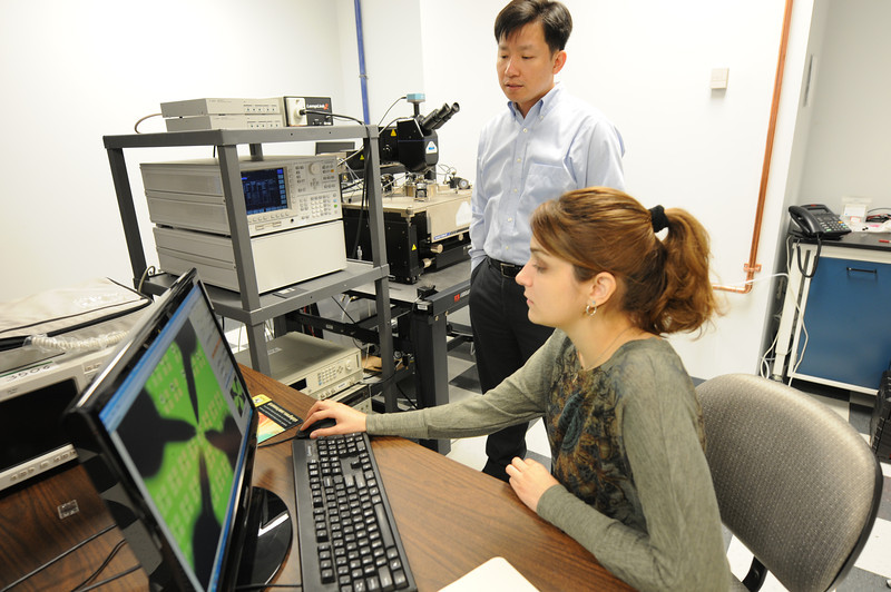 Graduate student Vaileia Georgiou working with Professor QiLiang Li measuring the silicon nanowire field effect transistor on silicon wafer. Photo by Evan Cantwell/Creative Services/George Mason University