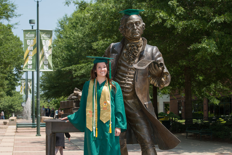 A graduating student poses by the Mason Statue at Fairfax Campus. Photo by Alexis Glenn/Creative Services/George Mason University
