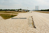 The crawler-transporter road which runs from the VAB (seen in the background) to launch pads 39A and 39B at the Kennedy Space Center. The chain link fence piece lying on the side of the road is used to smooth the rock on the road, by pulling it behind a truck.