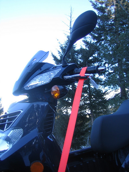 Tie down is fed through the hook and looped over the handlebar grip and brake.