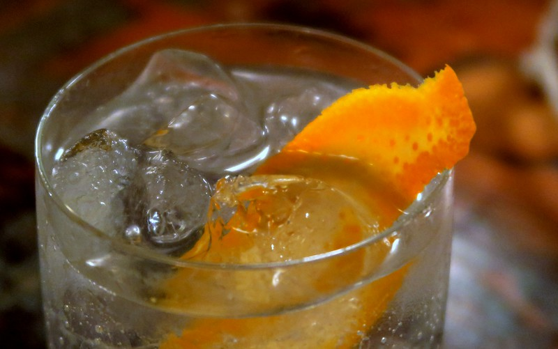 Gin and tonic with orange rind.