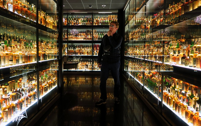 Inspecting all of the Whisky bottles on display at the Edinburgh Whisky Experience tour in Edinburgh, Scotland
