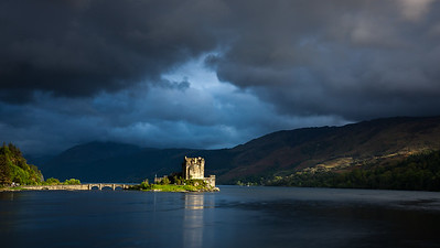 ray of light breaking through heavy storm clouds and hitting Eilean Donan Castle at Dornie  by Kyle of Lochalsh  Scotland