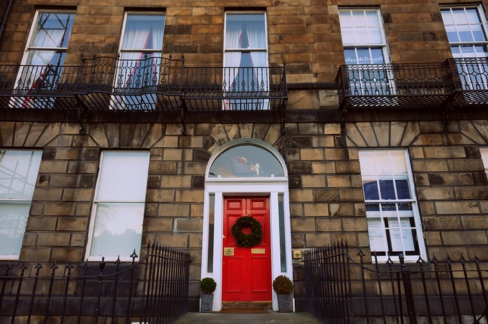Red door with a Christmas wreath in Edinburgh.