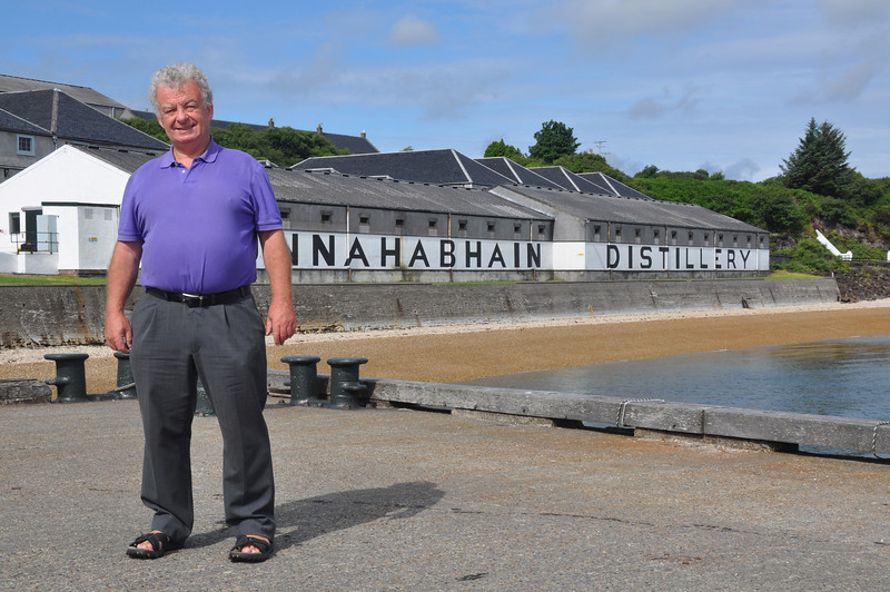 Ian Goodall back to his roots standing on Bonahaven pier. Bunnahabhain distillery in the background is one of eight working distilleries on the Isle of Islay