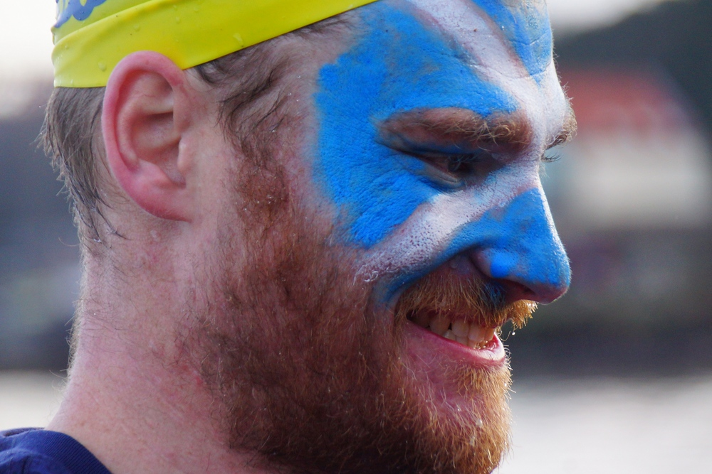 A man with the Scottish flag painted on his face stops to smile during the Loony Dook.
