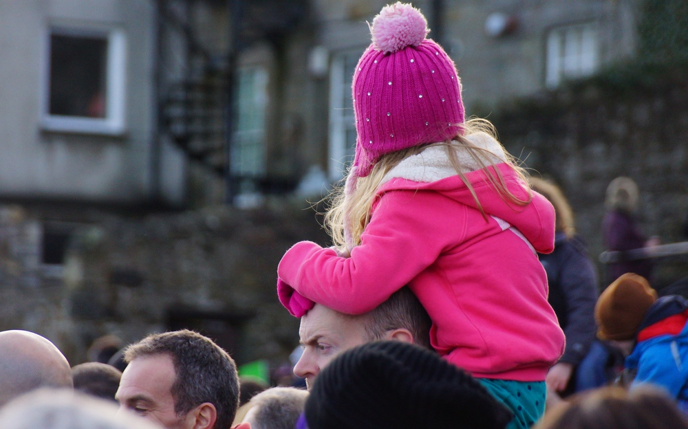 A girl wearing a warm pink fleece and toque sits on top of her Dad's shoulders while watching the Loony Dook in Edinburgh, Scotland.