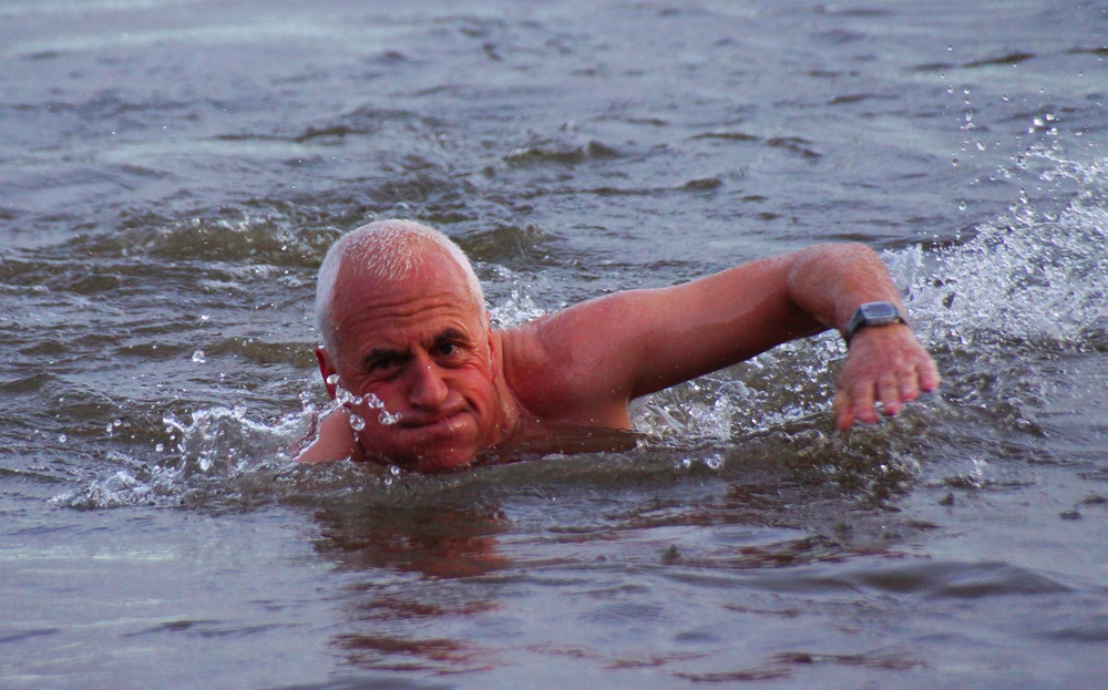 A man very confidently and bravely swims in the Firth of Forth during Loony Dook.
