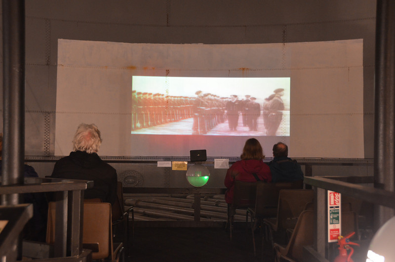 Lyness. Film is projected onto the inside wall of the old oil tank. 'Screen' is complete with rust streaks and rivets