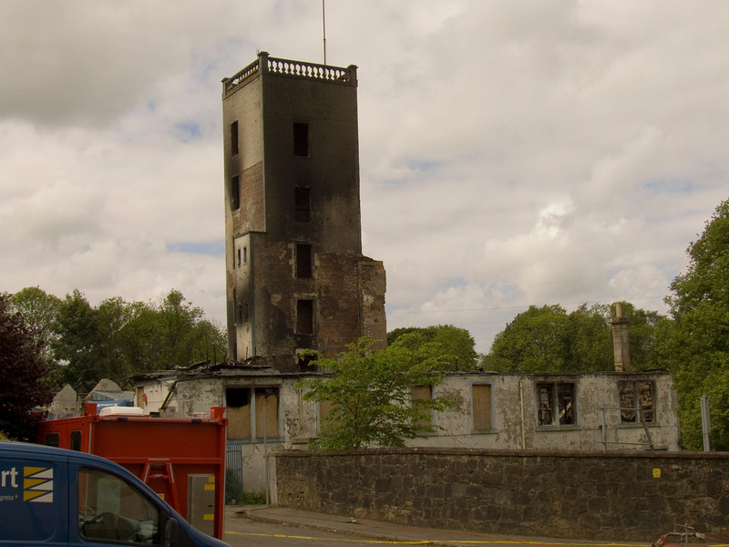 Burn out gate house, burnt out stair tower and a skip waiting to take the rubble of the demolished mill away