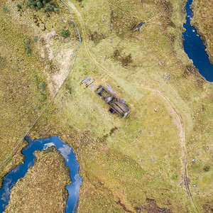 Looking down on the ruins of Lubnaclach Cottage, a remote and isolated herdsman's shelter close to the West Highland Railway Line near Corrour in the wild landscape of Rannoch Moor in the Highlands of Scotland.