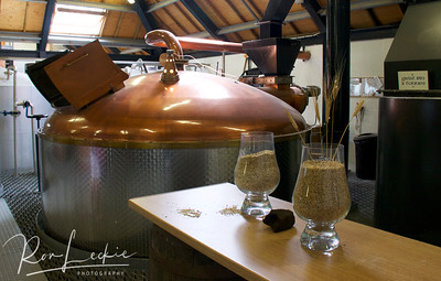 Isle of Arran, Lochranza Distillery: Malted barley, a lump of peat and grist in front of the Mash Tun where water is added to grist.