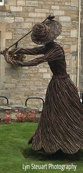 Woman golfer sculpture made from tree saplings.