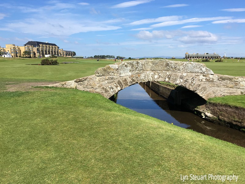 The old golf course at the Swilcan bridge at St. Andrews with the club house in the background (R) and the hotel on the (L)