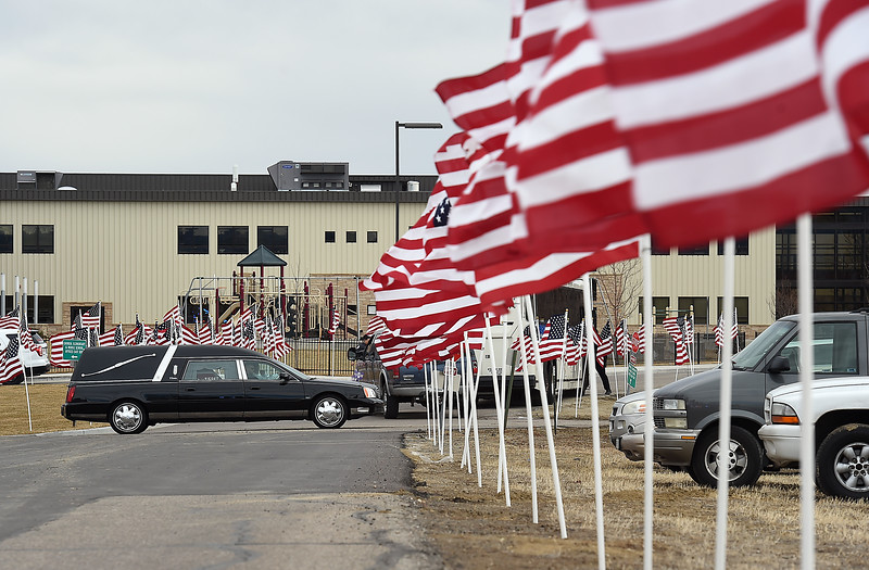 A procession makes its way past American flags at Rez Church after Scott VonLanken's memorial service Monday, Feb. 6, 2017, in Loveland. VonLanken, an RTD security officer, was killed while on duty in downtown Denver last week.  (Photo by Jenny Sparks/Loveland Reporter-Herald)