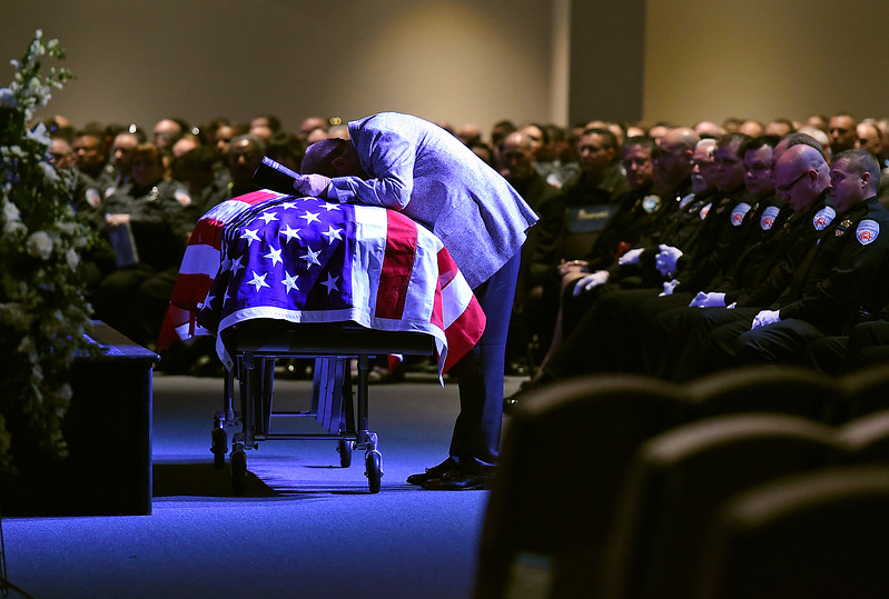 Rev. Nick Fair leans over his friend Scott VonLanken's flag draped casket before speaking about him during VonLanken's memorial service Monday, Feb. 6, 2017, at Rez Church in Loveland. VonLanken, an RTD security officer, was killed while on duty in downtown Denver last week.  (Photo by Jenny Sparks/Loveland Reporter-Herald)
