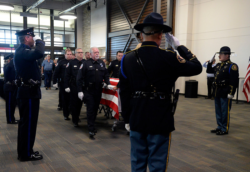 Loveland Police officers and Larimer County Sheriff's deputies salute as pal bearers bring Scott VonLanken's casket into the sancuary during his memorial service Monday, Feb. 6, 2017, at Rez Church in Loveland. VonLanken, an RTD security officer, was killed while on duty in downtown Denver last week.  (Photo by Jenny Sparks/Loveland Reporter-Herald)