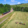 The new Borders Railway. Scene shows rail track and train heading north at Bowshank Tunnel, with farmer and tractor in field. Train has been added in Photoshop