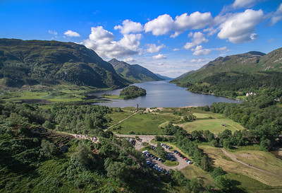 The Glenfinnan Monument and Loch Shiel on a sunny morning. Visitors gather at the viewpoint to watch the Jacobite Steam train passing the nearby viaduct.