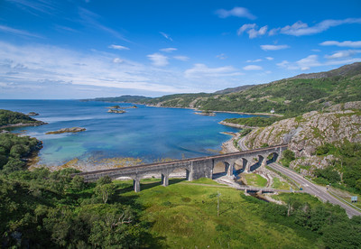 The Loch-nam-Uamh Viaduct, where the rail track passes through a tunnel carved from the rock face. Sunny day.