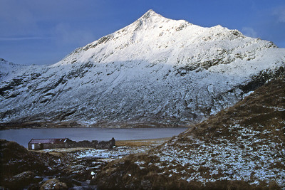 An Sgurr and the bothy.7am, 17/04/84~ There is something odd about the walk north from the Torrain Duibh bridge by the chain of lochs, under the wizardly Cona'mheall, through to Gleann Beag, something uncanny that I've never been able to put a name to, but this was the way I took on the dreich Easter Saturday of '84. The brawling Allt a'Gharbhrain was the first obstacle, requiring a mile-long detour upstream for a reasonable crossing, and the Allt Lair would have been the next but for a fallen tree which I swung across on. By now the rain had turned to snow, more Christmas than Easter I thought, and the pull up from Loch na Still was the entry to an Arctic landscape - I had a minute or so of quiet panic, quite disorientated (pre-GPS remember) by the absence of Loch Prille from where it surely should have been, until I realised that the wide flat white area I could make out through the gloom was in fact the loch, frozen and snow-covered at 1800'. Relief made the descent to the bothy swift and agreeable. The next day saw a very forgettable squelchy traverse of Seana Bhraigh in steady sleet, and a thigh-deep wade across the Corriemulzie river to Coiremor. After dark the wind veered from SW to NW, and by morning there had been a considerable dump of snow, down to bothy-level (1000'). I'd set my heart on a traverse of the compelling Sgurr (Creag an Duine on the OS map) back to Glenbeg, and having brought only 1 day's supplies a second night at Coiremor was an unattractive option, but I was very doubtful of the prudence of attempting the route. On the other hand a clear blue sky, the prospect of spectacular and unusual views, 'nothing-ventured-nothing-gained', conspired to make up my mind. Crossing the Allt a'Choire Mhòir some way above the loch to keep the boots dryish left me a long laborious way from the north ridge, so to gain height while the sun lasted I took to the vague eastern shoulder, itself heavily plastered with soft dry snow, waist-deep in places and slow going - a good 3 hours from bothy to an Sgurr, where the view did, I think, make it all worth while. I'd seen the Sgurr in profile from Seana Bhraigh in the heatwave May of '80 (all 6 Munros on the 18th, wearing just shorts, socks and boots, the peat-hags like rubber crazy paving) but had no idea of what to expect between it and the plateau, not in these conditions anyway. What I found had me casting around for any reasonable alternative, but there was none, so the bull's horns had to be grasped - a few years later on a wet summer day I found it a awkward little scramble, but in this deep unconsolidated snow, ropeless, it was desperate, a case of looking for the safest places to fall rather than for the easiest route. (If this seems a strange logic, consider my position, alone on a candidate for the title of most remote and least visited peak in Scotland, in a world still innocent of mobile phones - any disabling fall would have been fatal.) In fact I took two little falls, the first trivial and lighthearted, but the second a real 'shi-i-i-i-i-i-i-i-i-i- . . .' event which left me shaken but not much bruised, this luckily the last of the difficulties. Interestingly (to me anyway), J. A. Parker and friend had been faced with much the same problem in March 1930, and solved it with a traverse on the west side of the ridge (SMC Journal no.110, Nov. 1930, pp.73-76), but each to his own, that was one of the alternatives I didn't fancy. A few more photos before the sun faded, with cloud building from the south, a visit the the Seana Bhraigh summit, then down to Glenbeg and a reflective night before the fire. The Prille - Still - Lair - Gharbhrain walk-out the next morning was wet again, and as fey as ever