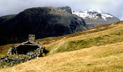 Fainasheen (Feithe na Sine), with Mullach Coire Mhic Fhearchair.  16/04/80  ~ Within living memory this was a bothy, but even by 1980 it was in a state of collapse, of use only to the desperate (but what a situation!). Its dilapidation has continued, and the chimney stack and what remained of the roof are now gone.
