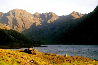 Sgurr a'Ghreadhaidh, Sgurr a'Mhadaidh, and Bidein Druim nan Ramh from Loch Coruisk.  6am, 12/6/95  ~ an Dorus is the v-shaped gap left of centre.