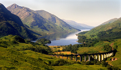 The Glenfinnan viaduct, Loch Shiel, and Sgurr Ghiubhsachain.  11.30am, 05/08/95  ~ This and the following 19 shots were all taken in the course of a weekend, one  which ranks with the very finest I have ever spent among the hills. It was wedged between a shift which finished at 10pm on Friday and one which started at 10pm on Monday,  and it involved an element of burning the candle at both ends, but it glows in my memory like a diamond on a heap of dross.  Glenfinnan - Beinn an Tuim and the intervening bumps to Streap - Sgurr Thuilm to Coireachain with an overnight stop at the midway point of Beinn Gharbh - head of Loch Morar - Sgurr nam Meirleach for another night stop - along the North Morar ridge and down to Tarbet - mail-boat to Mallaig - train back to Glenfinnan. Weather was - well, you'll see.