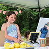 Chloe McNabb, 7, of Ayer buys leomade from Scout Maloney, of Ayer who sells lemonade at the Ayer end of the Nashua River Rail Trail on Sunday to raise money for immigrant children on the border.  SENTINEL & ENTERPRISE JEFF PORTER