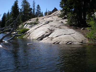 Canoe Orienteering Point Number 2.  The chalk number 2 is hard to see,  but it is on the granite near the water line, at the point closeest to the dead branch in the water.