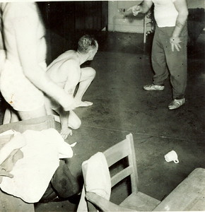 5 Dec 1952Going away bash for Skipper Ruse! Lt Ed Thompson preparing for wrestling match in classroom aboard Gate Vessel #1. Pierre Belley (Stoker) was Referee.