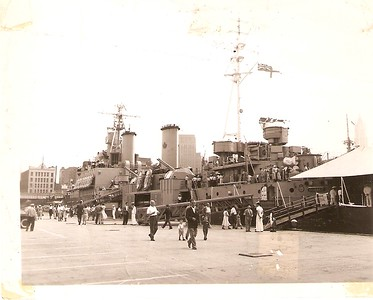 picture of HMCS QUEBEC(the former Royal Navy HMS UGANDA), I don't know where it was tied up, but it was in the Summer, and it was in warm weather - note the canvas tent erected over part of its deck, and every sailor in their summer white uniforms.