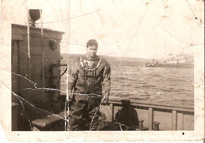 The Diver in photo all crinkled up, standing on the deck of a small boat(maybe a Tug or Tender, might even be the EDITH)is unknown to me, however he is one of the Naval Divers I would believe, and I would suggest that the photo was not taken in the Arctic(too many small boats for that area)and was most likely taken somewhere in the Maritime Provinces when looking at the water, boats and far shoreline.
