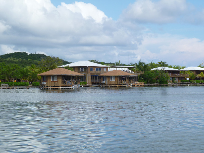 Two overwater bungalows with main resort building in background.
