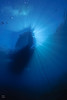 """Sun beams framing dive boat Magician, at """"Little Flower"""", San Clemente Island."""