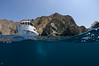 Cape of Cortez, Catalina... Magician Dive Boat, looking pretty with the island in the background.  Those are divers' bubbles in the lower half of the photo.