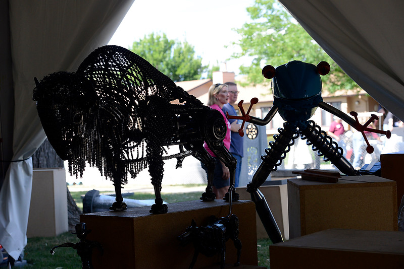 "A sculpture of a buffalo and a frog titled ""Heart and Sould"" and Coqui"" by artist Tim Little are set in their places Thursday, Aug. 11, 2016, as another sculptor, Scott Luken and his wife Angie Luken, work on setting up his art in the background in preparation for the upcoming Sculpture in the Park at Benson Park Sculpture Garden in Loveland. Artist from all over the counrty set up their sculptures for the juried show and sale. Little uses found objects to create his sculputres, including bicycle chains for the buffalo. (Photo by Jenny Sparks/Loveland Reporter-Herald)"